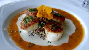 Seared Diver Scallops with heirloom tomato vinaigrette and fire roasted pepper cream.