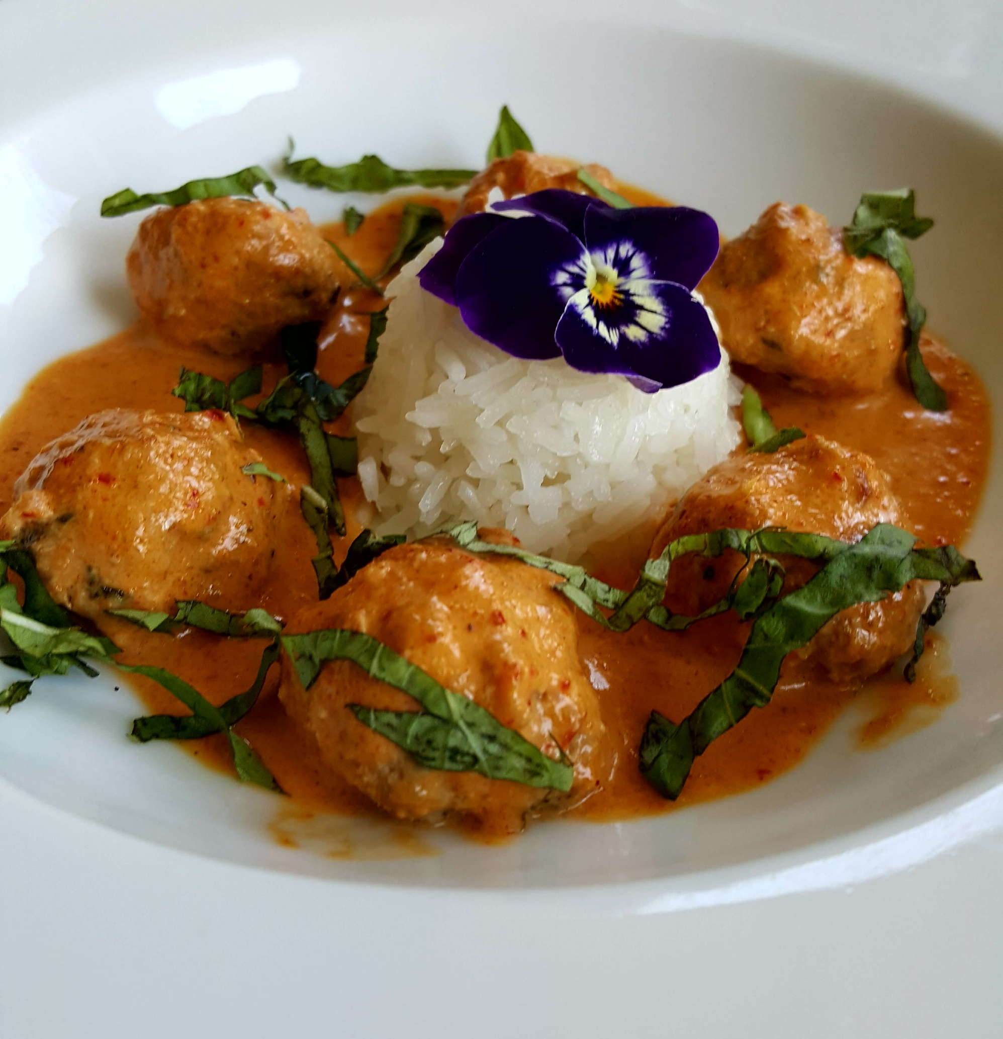 Thai Pork Meatballs with jasmine rice and red curry sauce.
